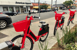 Three red JUMP bikes on University and 4th Ave in San Diego, CA.