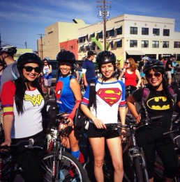 Four wonder women on their bikes wearing tee-shirts with comic book logos on a sunny day.